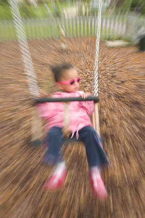 A zoomed shot of a young mixed race girl playing on a swing Stock Photo - 275938