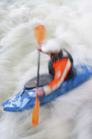 paddler: A motion blurred shot of a kayaker paddling in whitewater