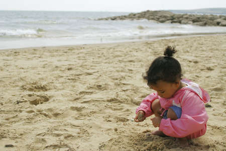 A young mixed race girl plays alone on a sandy beach Stock Photo - 275945