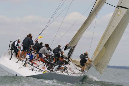 An open 65 yacht all crewed up and racing hard.