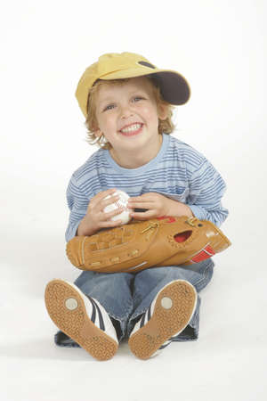 A young boy holding a baseball and wearing adult sized baseball cap and glove - studio shot in a portrait format photo