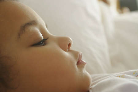 közel: A young mixed race girl eyes half closed and nearly sleeping Stock fotó