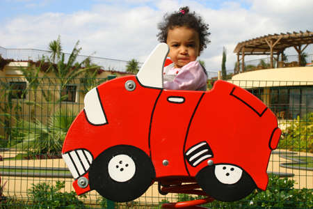 A young mixed race girl sitting in a red car on a spring at a childs playground