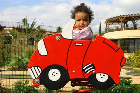 Una joven mestiza ni�a sentada en un coche rojo en un muelle a un ni�o de juegos  Foto de archivo