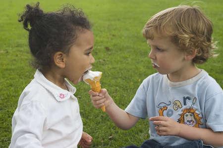 egoista: Un ni�o y ni�a de compartir un cono de helado  Foto de archivo