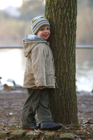 cousin: A young boy playing hide and seek behind a tree