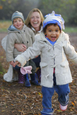 A beautiful mixed race girl runs towards the camera laughing while over her shoulder you see a young mother with her son. photo