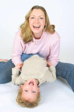 Una madre joven y su hijo que juegan y que r�en junto Foto de archivo
