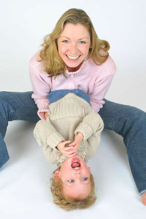 female likeness: A young mother and her son playing and laughing together.