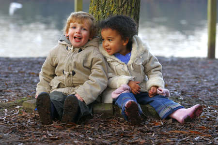 A little blond boy and a mixed race girl sitting resting at the base of a tree. photo