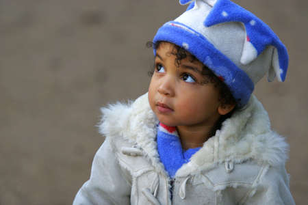 hair wrapped up: A young mixed race girl looks innocently upwards Stock Photo