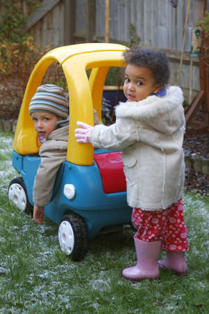 cousin: A little girl pushing a small boy in a giant toy car