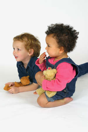 Two young children holding bears and looking at something - probably a television!