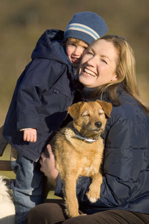 A mother her young son and the family dog cuddle up in the winter sun