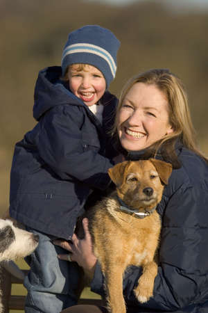 mother on bench: A mother, her young son and the 2 family terriers sitting on a park bench laughing and wrapped up warm against the cold Stock Photo