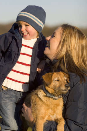 A mother her young son and the family dog together laughing on a park bench. Stock Photo