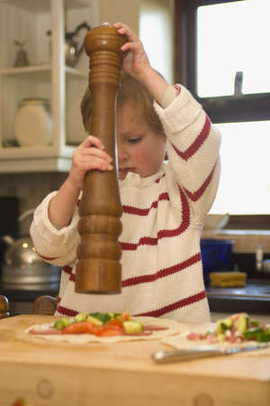 A young boy grinds pepper from a huge mill onto a tortilla wrap he is preparing. photo