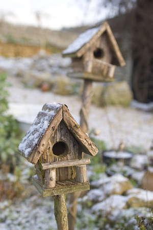 tomar prestado: Dos cubiertas de nieve cajas de aves, uno en el punto de mira, uno.  Foto de archivo