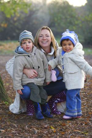 A young family having a walk in a park wrapped up warm against the cold.