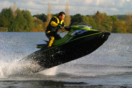 A jet ski and its rider leap clear of the water