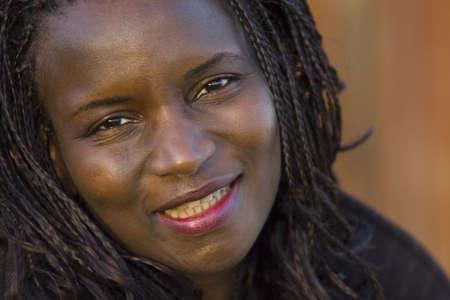 Una mujer negra joven hermosa con el pelo trenzado que sonr�e para la c�mara fotogr�fica Foto de archivo
