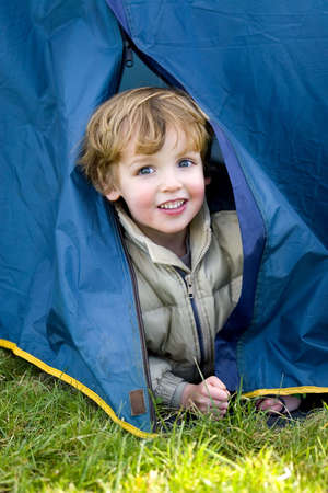 A young boy emerges from a tent on a camping trip Stock Photo