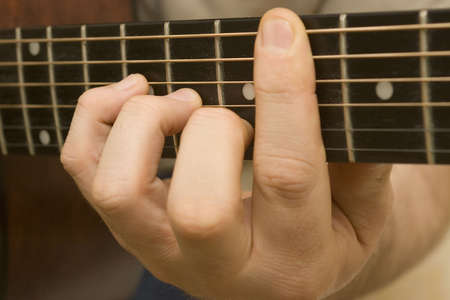 fret: Close up shot of a chord on the fret board of an acoustic guitar
