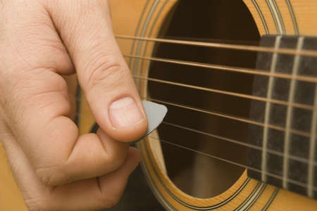 Close up of a guitarist playing a guitar with a plectrum Stock Photo