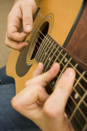 Shot of hands playing an acoustic guitar with a plectrum Stock Photo