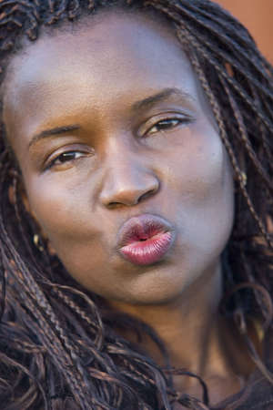 A beautiful young black woman blowing a kiss to the camera photo