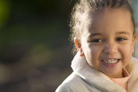 english girl: A beautiful mixed race girl laughing and backlit by sunshine