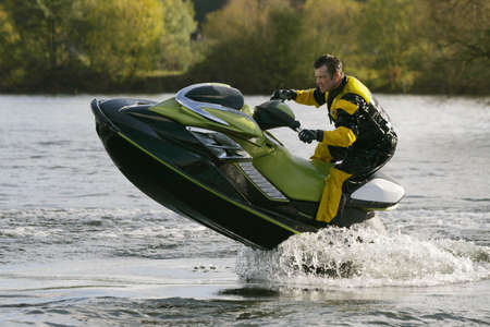water skier: A jet skier gets his personal water craft out of the water