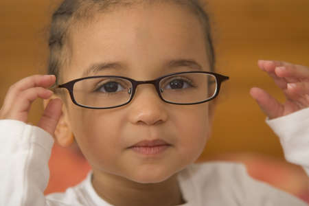 bookish: A beautiful young mixed race girl wearing oversized glasses Stock Photo