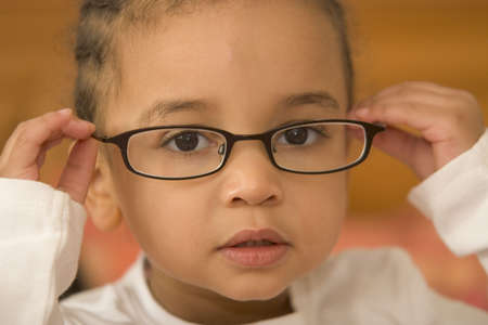 A beautiful young mixed race girl wearing slightly oversized glasses