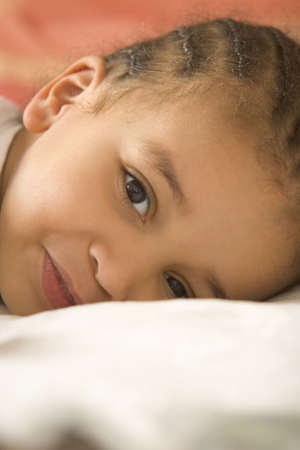 woken: A beautiful young mixed race girl lying on her pillow having just woken up