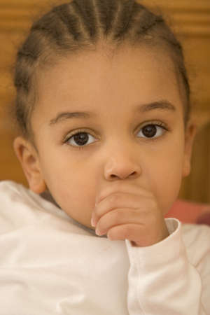 A beautiful young mixed race girl sucking her thumb photo