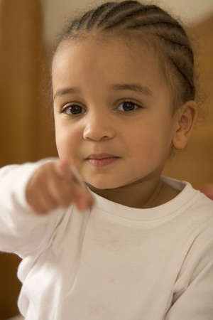 A beautiful young mixed race girl points at the camera Stock Photo