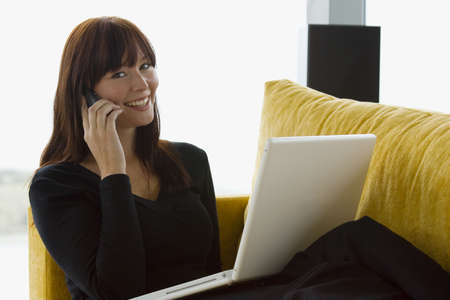 A young woman working at home on her laptop computer while talking on a mobile phone. Stock Photo