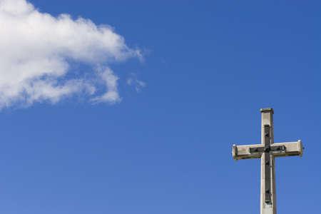 crusade: A crucifix shot against a blue sky with a white cloud