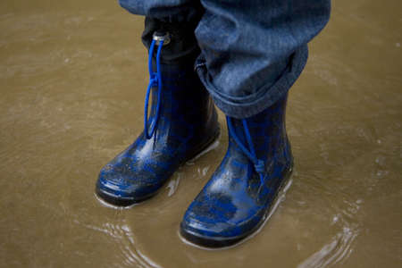 A little boy in blue boots standing in a muddy puddle photo