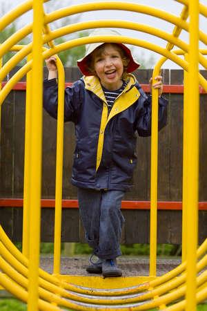 climbing frame: Un giovane ragazzo guardando attraverso un tunnel di arrampicata su un telaio