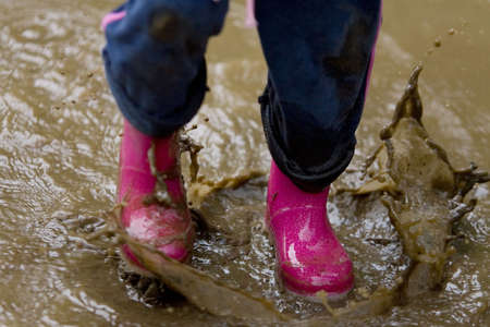 A little girls pink boots splashing in a muddy puddle photo