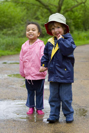 A little boy and girl wearing wellington boots holding hands and sharing a puddle in a park photo