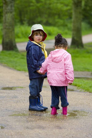 wellingtons: A little boy and girl wearing wellington boots, holding hands and sharing a puddle in a park
