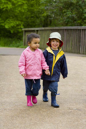 A little boy and girl wearing wellington boots holding hands and walking through a country park photo