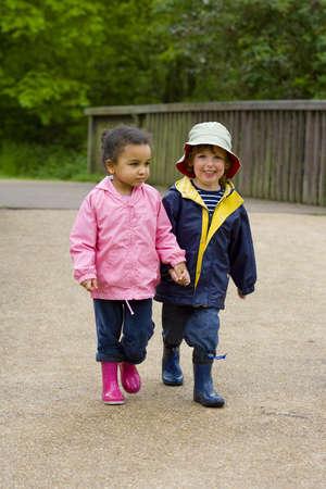 country park: Un ni�o y ni�a llevaba botas wellington la mano y caminar a trav�s de un parque pa�s