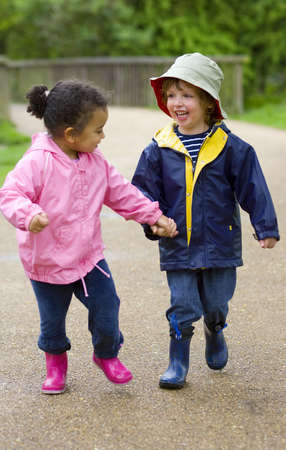 wellingtons: A little boy and girl wearing wellington boots holding hands and running through a country park