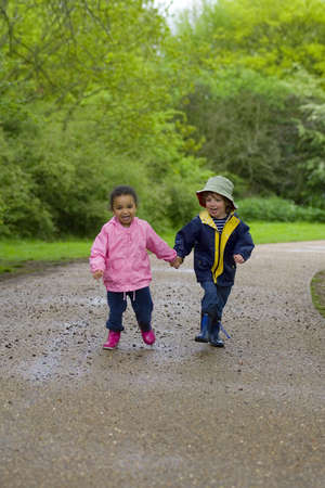 A little boy and girl wearing wellington boots holding hands and running through a country park