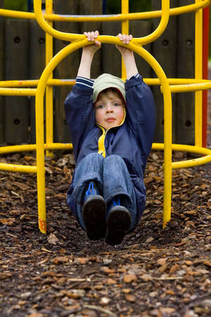 climbing frame: Un ragazzo giovane si � vestito in su contro il tempo che oscilla su una struttura rampicante