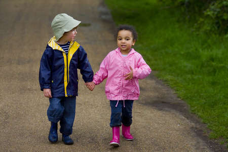 A little boy and girl wearing wellington boots holding hands and walking through a country park Stock Photo